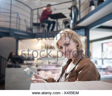 Retrato de mujer sonriente con tablet PC en cafe Foto de stock