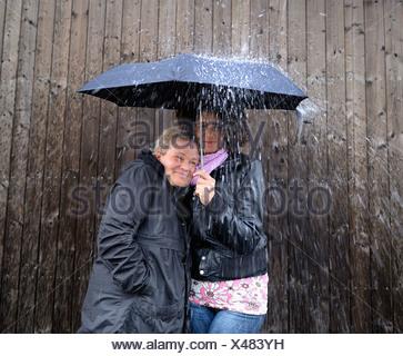Dos mujeres bajo un mismo paraguas.