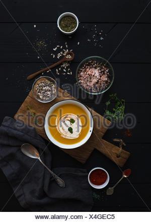 Sopa de calabaza con crema, semillas y especias en rústicas recipiente de metal en plancha de madera más grunge fondo negro. Vista superior Foto de stock