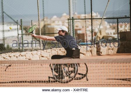 Adulto medio austríaco tenista paralímpico jugando en cancha de tenis
