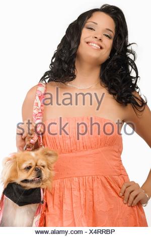 Retrato de una joven mujer que llevaba un perro Pomerania en una bolsa y sonriente