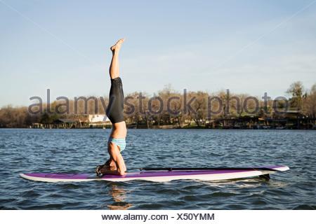 Una mujer que hace a hacer el pino en un paddle board en el lago