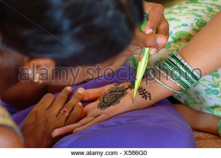La mujer que recibe un tinte de henna mendhi ( ) diseño en su mano antes de su boda india