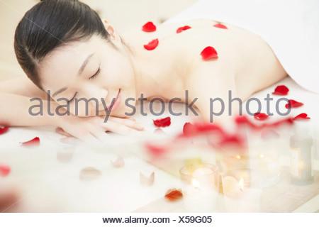 Mujer cubierto de pétalos de rosa