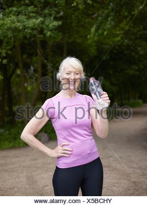 Mujer de edad bebiendo de la botella de agua