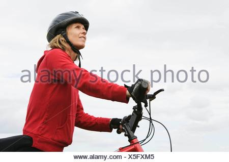 Mujer ciclista empujar bicicleta