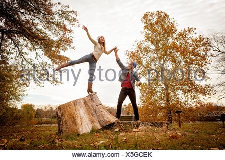 Pareja joven jugando en tocón de árbol en otoño park