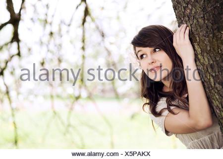 Hermosa joven escondiéndose detrás del tronco de un árbol. Debica, Polonia.