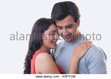 Romántica pareja joven sonriente contra el fondo blanco.