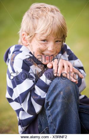 Muchacho sentado afuera, sucio y sonriente