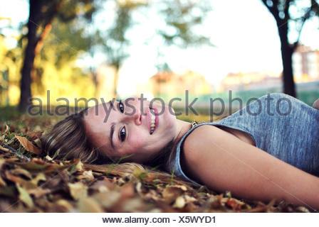 Retrato de mujer sonriente tumbado sobre hojas de otoño