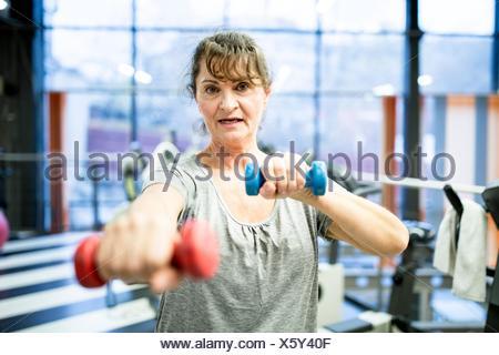 Liberados de la propiedad. Modelo liberado. Retrato mujer sosteniendo senior pesa en el gimnasio.