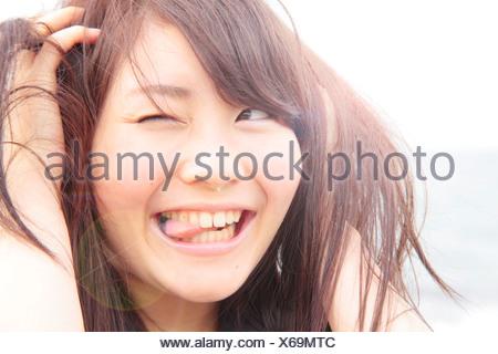 Retrato de mujer joven, las manos en el cabello, lengua fuera