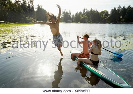 Par remando barco, hombre saltando en el lago, Seattle, Washington, EE.UU. Foto de stock
