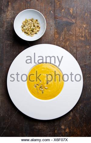Sopa de calabaza con semillas de calabaza sobre fondo de madera