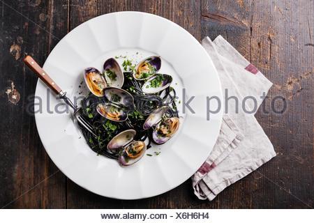 Pasta con marisco almejas Spaghetti vongole sobre placa blanca sobre fondo de mármol oscuro