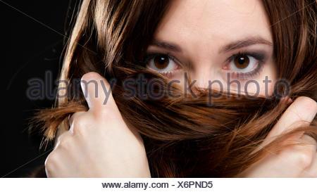 Closeup mujer cubre el rostro por largos pelos marrones