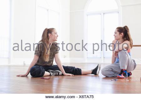 Dos chicas adolescentes sentados en el piso chateando en ballet school