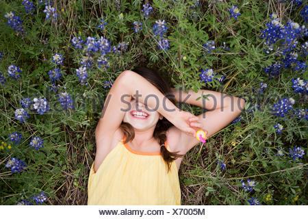 Una niña acostada sobre su espalda con su brazo por encima de los ojos.