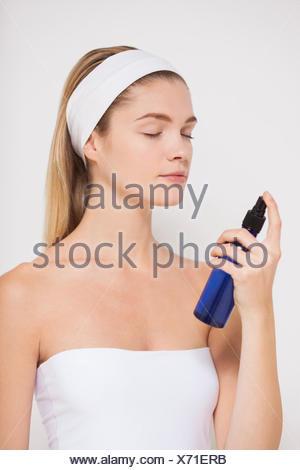 Bella mujer pulverizar agua sobre su cara