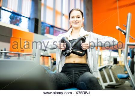 Liberados de la propiedad. Modelo liberado. Retrato de mujer joven con máquina de remo en el gimnasio.
