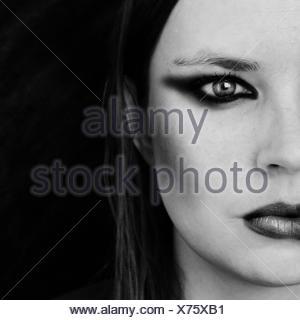 En primer plano el retrato de mujer joven contra fondo negro Foto de stock