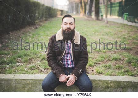 Joven hombre barbado en estacionamiento
