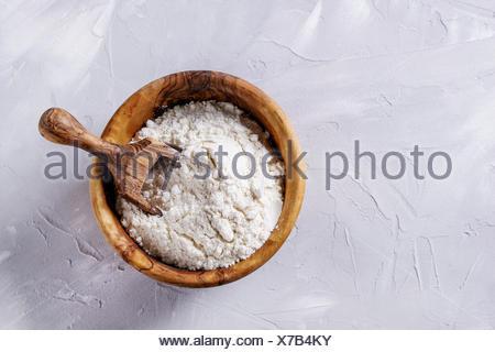 La madera de olivo bowl con harina de trigo y boca para hornear en casa. A lo largo de hormigón gris de fondo. Vista superior, espacio de copia Foto de stock