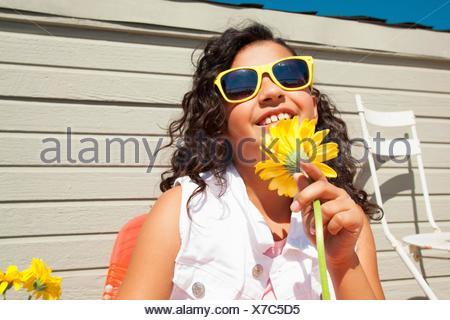Retrato de chica que llevaba gafas de sol amarillo girasol holding en el patio
