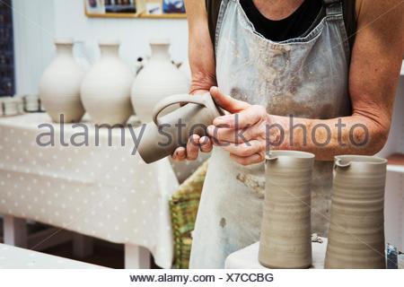 Un alfarero manejo de una olla de barro húmedo, suavizando la parte inferior y prepararla para alimentación de hornos.