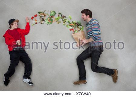 El hombre y el muchacho equilibrando las verduras