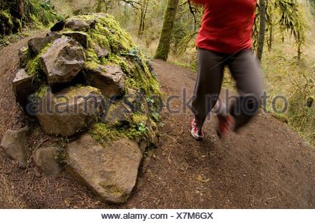 Una mujer corriendo un sendero a través de un bosque de musgo verde en Silver Falls State Park, Oregon, USA.