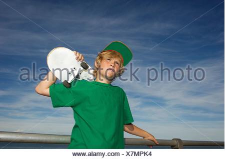 Retrato de niño sosteniendo el monopatín sobre el hombro