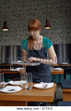 Mujer adulta media preparación de mesa en restaurante