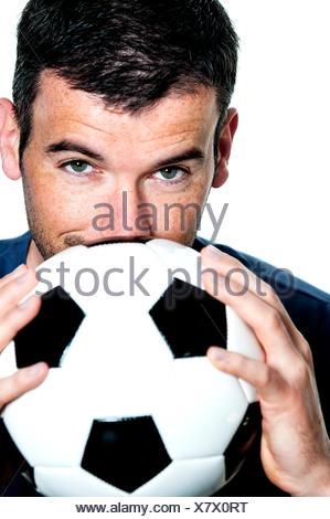 Primer plano de apasionado jugador de fútbol con balón blanco y negro Foto de stock