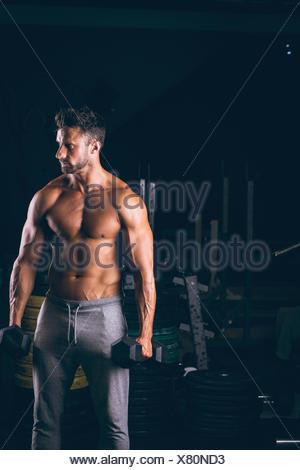El hombre muscular el ejercicio con pesas Foto de stock
