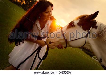 Retrato de mujer de pie con su caballo Foto de stock