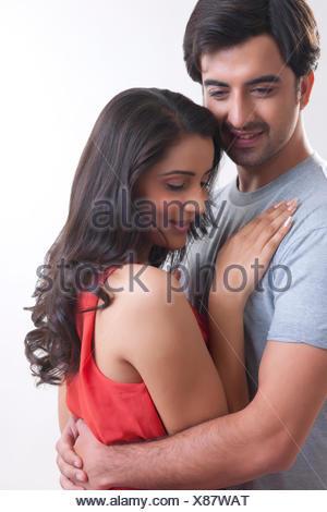 Romántica pareja joven abrazando contra el fondo blanco.