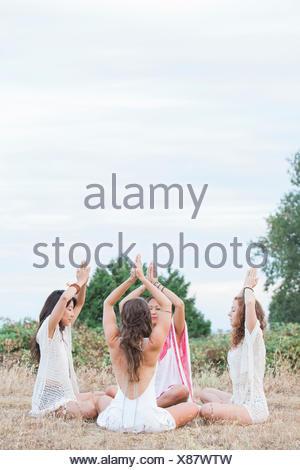 Boho mujer meditando con las manos entrelazadas sobrecarga en círculo en ámbito rural