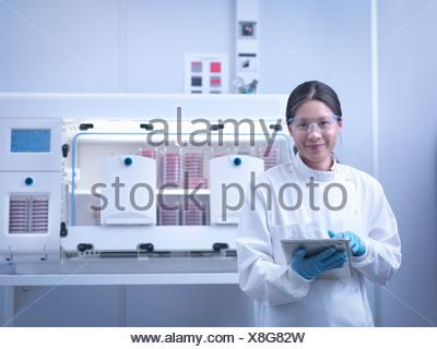 Retrato de científico con cultivos bacterianos dentro de estaciones de trabajo de laboratorio