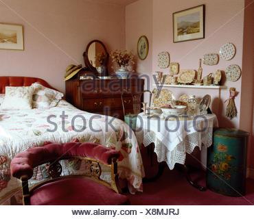 Silla tapizada de terciopelo rosa debajo de la Cama con