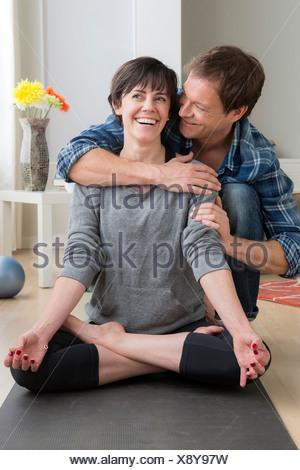 Mujer haciendo yoga en casa, hombre abrace su Foto de stock
