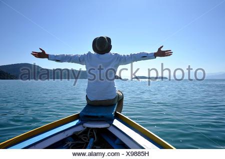 Hombre joven sentado en la proa de un barco de pesca con los brazos abiertos, Bahía de Paraty o Parati, Estado de Rio de Janeiro, Brasil