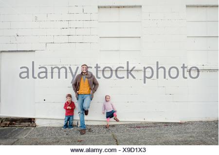 Mitad hombre adulto y su hijo e hija recostada contra la pared, Retrato