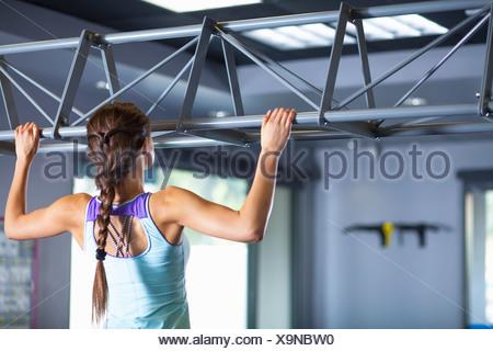 Mujer joven haciendo chin ups