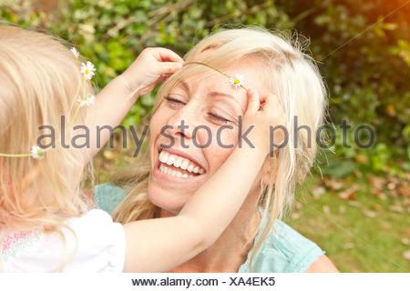 Cerca del infante femenino colocando daisy chain en el cabello de la madre en el jardín