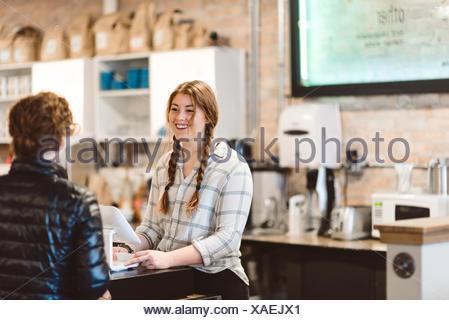 Cajero asistiendo al cliente en cafe
