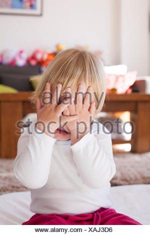 Retrato del bebé caucásica rubia diecinueve meses de edad que cubre su rostro con las dos manos la camisa blanca.