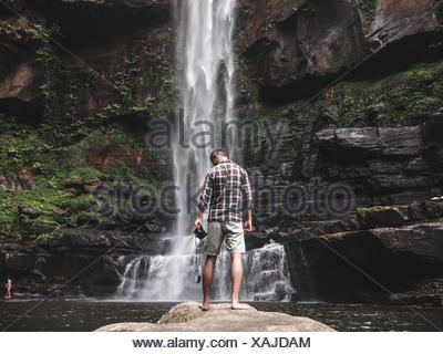 Vista trasera del hombre de pie sobre una roca contra la cascada