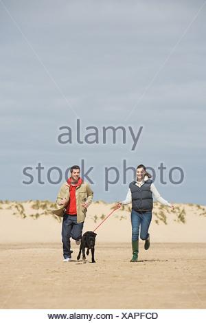 Par corriendo en la playa con perro Foto de stock